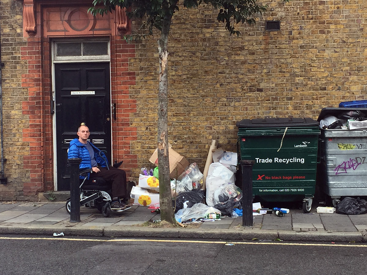 George Hornby in his wheelchair trying to get passed commercial rubbish on the street of Herne Hill