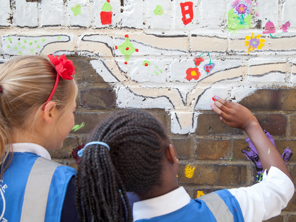 Schools children painting a mural with their fingers in Brockwell Passage, SE24