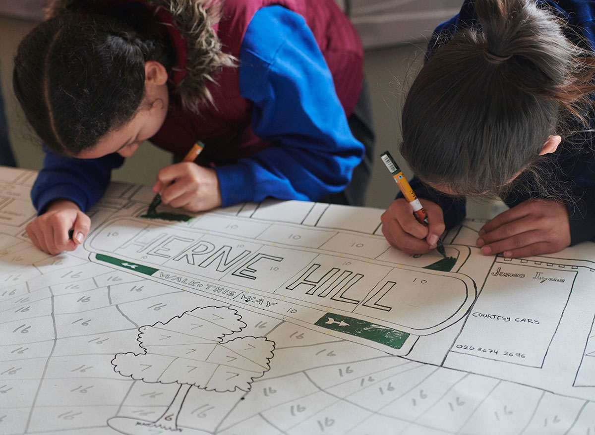 Herne Hill Mural being coloured in by children in Station Hall, Herne Hill
