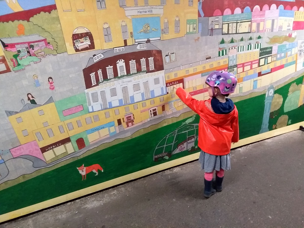 Young child pointing to the colouring in on the record breaking Herne Hill mural