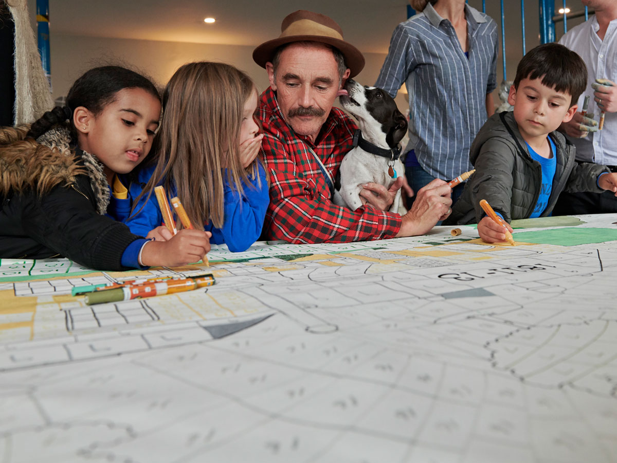 Mark Rylance being licked by his dog amongst school children colouring in the Herne Hill mural