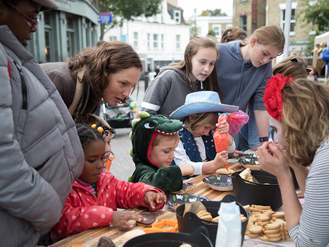 Children and parents decorating biscuits with Carolina Fox in Herne Hill
