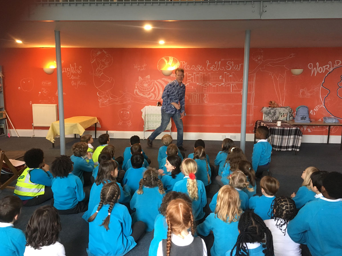 School children watching a performer in Station Hall, Herne Hill during Book Week 2019