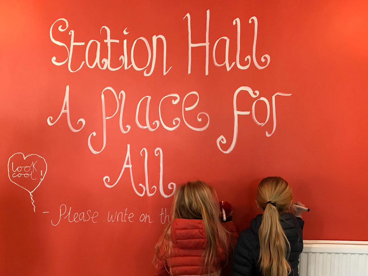 Two children writing ideas on the wall of community space Station Hall in Herne Hill
